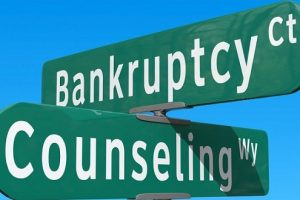 the words bankruptcy and counseling written on two green street traffic signs